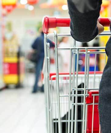 Lady pushing shopping cart in supermarket
