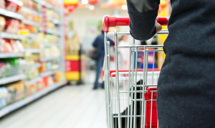 women pushing shopping cart in supermarket