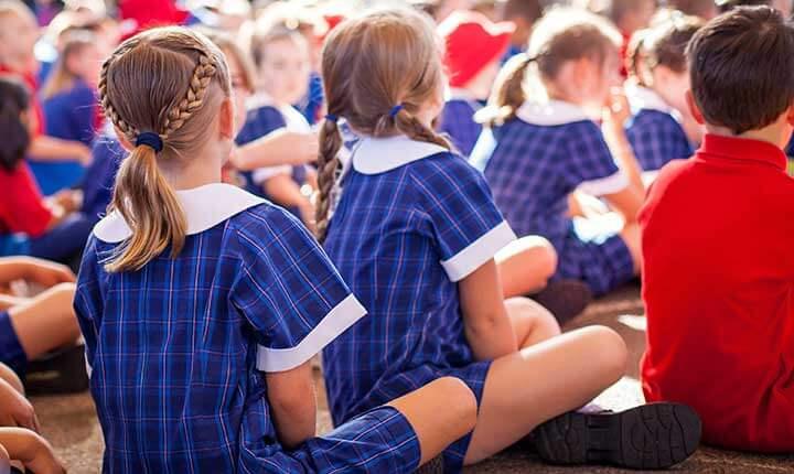 Children in school uniform sitting at parade